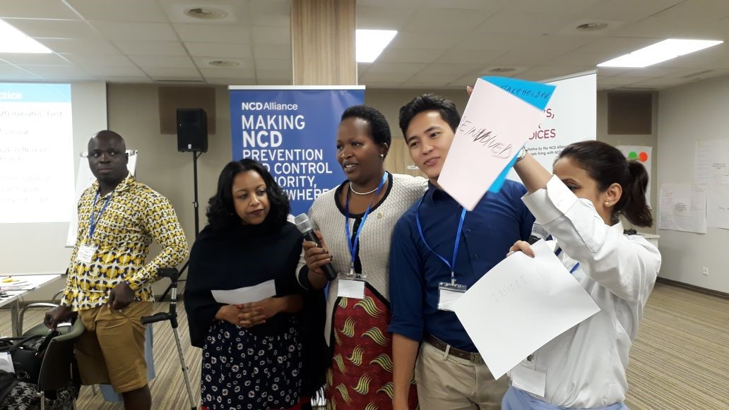 People holding microphone and signs in front of NCD Alliance poster